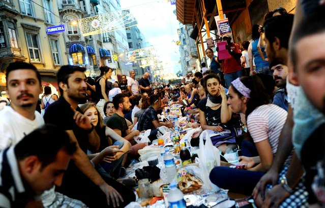 Turkish anti-government protesters take a break to mark the end of the first day of Ramadan, July 9, 2013 in Istanbul. (Photo by Bulent Kilic/AFP Photo)