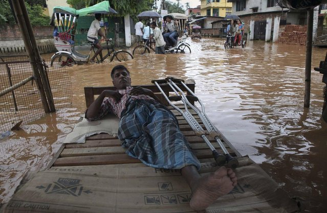 A physically disabled man rests as commuters on rickshaw cross a waterlogged street in Gauhati, India, Tuesday, July 16, 2013. (Photo by Anupam Nath/AP Photo)