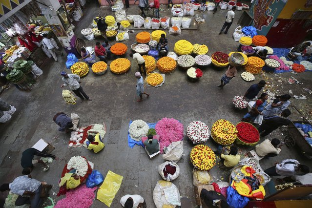 Flower vendors wait for buyers at a wholesale market in Bengaluru, India, Thursday, September 24, 2020. The nation of 1.3 billion people is expected to become the COVID-19 pandemic's worst-hit country within weeks, surpassing the United States. (Photo by Aijaz Rahi/AP Photo)