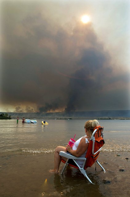 Jody Erickson, of Kent, Wash., watches the Colockum Tarps fire from her beach chair Monday, Juy 29, 2013, while sitting on the bank of the Columbia River at the Crescent Bar Resort south of Malaga, Wash. The fire is estimated at 15,000 acres in size. (Photo by Don Seabrook/AP Photo/The Wenatchee World)