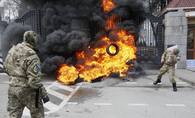 """A serviceman from the battalion """"Aydar"""" throws a tyre on a fire during a protest against disbanding of the battalion in front of Ukraine's Defence Ministry in Kiev, February 2, 2015. (Photo by Valentyn Ogirenko/Reuters)"""