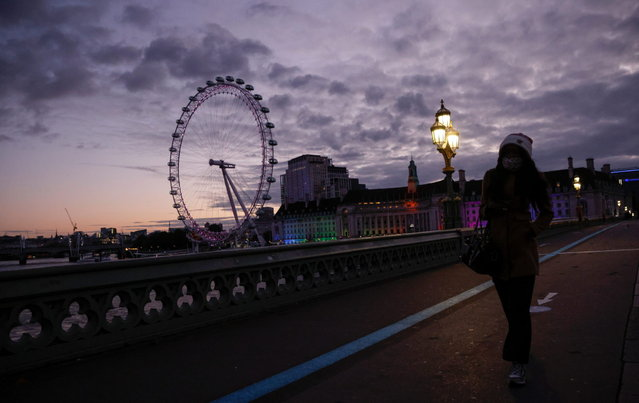 A person walks across the Westminster Bridge before sunrise, amid the coronavirus disease (COVID-19) outbreak, in London, Britain on October 16, 2020. (Photo by John Sibley/Reuters)
