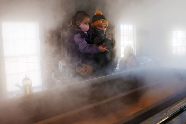 Visitors watch as sap from maple trees is boiled down into maple syrup in the evaporator in the sugar house at Hollis Hills Farm in Fitchburg, Massachusetts, U.S., March 13, 2021. (Photo by Brian Snyder/Reuters)