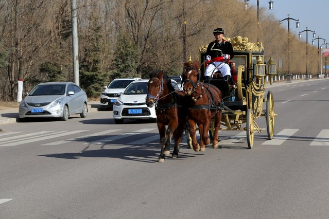 Bai Dijun rides his homemade carriage which resembles the carriage used by the British royal family, in Liangping, Gansu province, December 27, 2015. Bai makes money from renting the carriage to tourists and as props to commercial performance organizers, according to local media. (Photo by Reuters/Stringer)