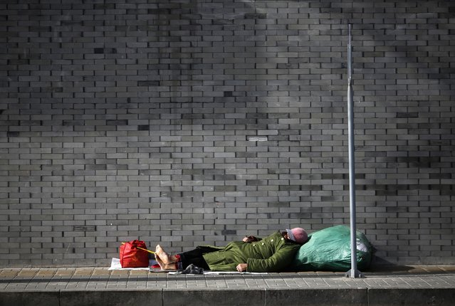 A man takes a nap on a street in Beijing February 6, 2015. (Photo by Kim Kyung-Hoon/Reuters)