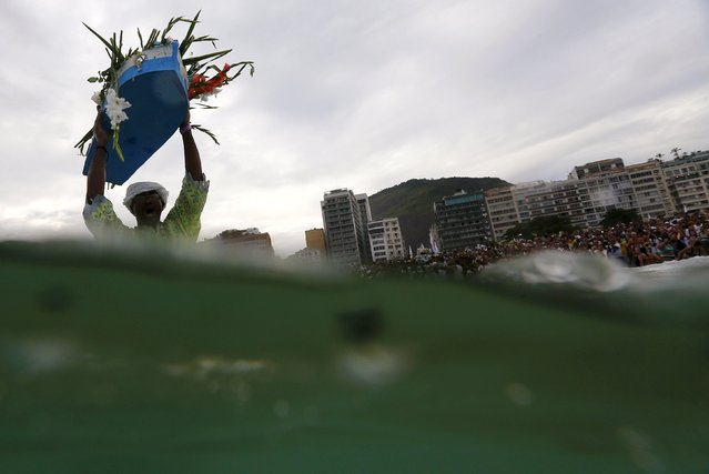 A follower of the Afro-Brazilian religion Umbanda carries offerings for Iemanja, goddess of the sea, at Copacabana Beach in Rio de Janeiro December 29, 2015. Worshippers present gifts to the sea goddess at the end of every year, to give thanks and ask for blessings for the upcoming new year. (Photo by Ricardo Moraes/Reuters)