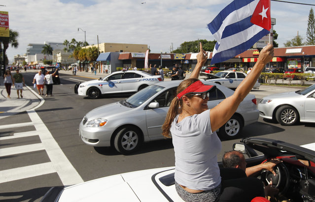 """Pedestrians and vehicles are seen at the end of the closed  street near the iconic Cuban restaurant """"Versailles"""" Saturday November 26, 2016 in the Miami neighborhood of Little Havana react the day after Cuban President Raul Castro announced  his brother and former Cuban President, Fidel Castro's death in Cuba the night before. (Photo by Andrew Innerarity)"""