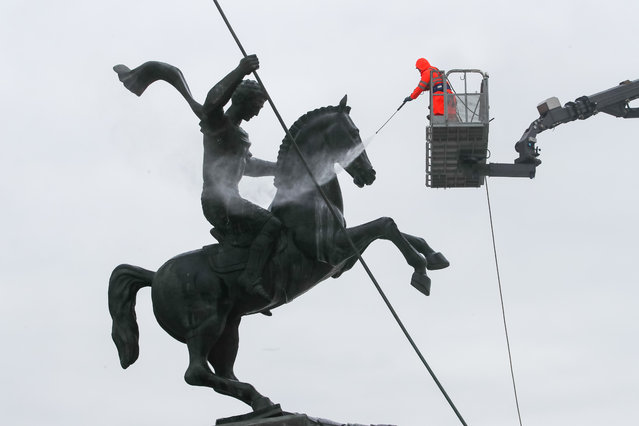 A Gormost worker power washes an equestrian statue of St George at the Victory monument during spring cleaning at the WWII memorial on Poklonnaya Gora in Moscow, Russia on March 17, 2021. (Photo by Sergei Karpukhin/TASS)