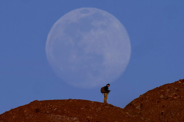 The nearly-full moon rises beyond a hiker at Papago Park on Thursday, February 25, 2021, in Phoenix, Arizona. (Photo by Charlie Riedel/AP Photo)