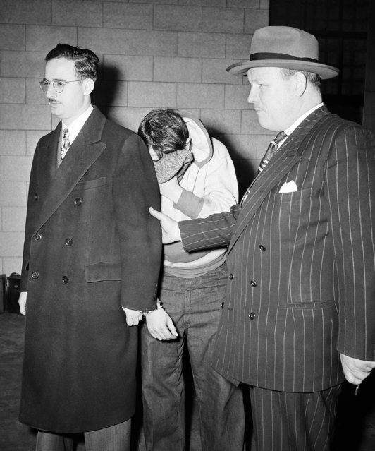 Julius Rosenberg, left, 32-year-old electrical engineer, is led into the Federal Courthouse, in New York City, April 5, 1951 where he received the death sentence for his participation in supplying Russia with secret material about the atom bomb. He is handcuffed to another prisoner. Both are in custody of a U.S. deputy marshal, right. Rosenberg's wife, Ethel, also received the death sentence at the same time. (Photo by AP Photo)
