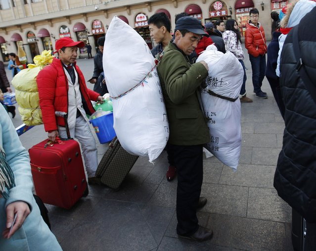 A man carries sacks as he stand in a line to enter a platform at a railway station in Beijing February 16, 2015. (Photo by Kim Kyung-Hoon/Reuters)