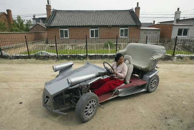 Zhang Jinduo's wife tries on a self-made racing car on the outskirts of Shenyang, Liaoning province May 10, 2008. Zhang, the 53-year-old local farmer made the racing car with the help of his son who is a car mechanic. The car is equipped with a rear-mounted motorcycle engine and can achieve 60-80 km per hour, according to local media. (Photo by Reuters/Stringer)
