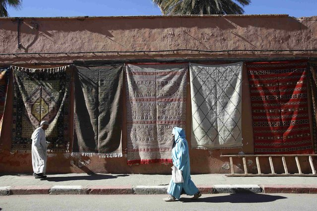 A man and a woman, wearing traditional clothing, walk along a street in the city of Marrakech December 10, 2014. (Photo by Youssef Boudlal/Reuters)