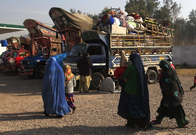 An Afghan refugee family walks past trucks loaded with their belongings as they prepare to go back to Afghanistan with others, at the United Nations High Commissioner for Refugees (UNHCR) office on the outskirts of Peshawar February 13, 2015. (Photo by Fayaz Aziz/Reuters)
