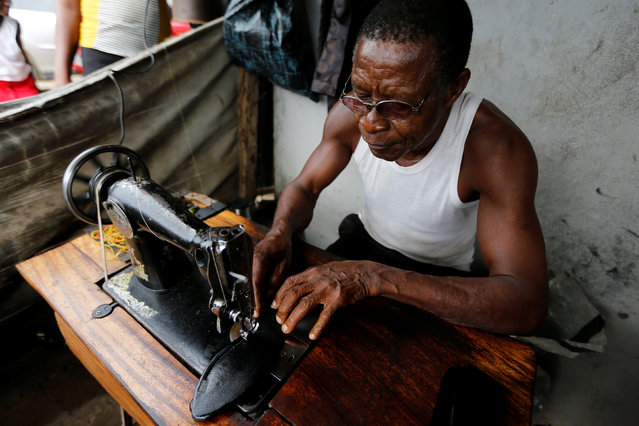 A man sews a shoe in Araria market in Aba, Nigeria August 19, 2016. (Photo by Afolabi Sotunde/Reuters)