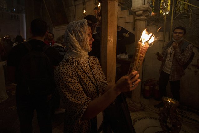 A Christian pilgrim holds candles during the ceremony of the Holy Fire at Church of the Holy Sepulchre, where many Christians believe Jesus was crucified, buried and rose from the dead, in the Old City of Jerusalem, Saturday, May 1, 2021. Hundreds of Christian worshippers took use of Israel's easing of coronavirus restrictions Saturday and packed a Jerusalem church revered as the site of Jesus' crucifixion and resurrection for an ancient fire ceremony ahead of Orthodox Easter. (Photo by Ariel Schalit/AP Photo)