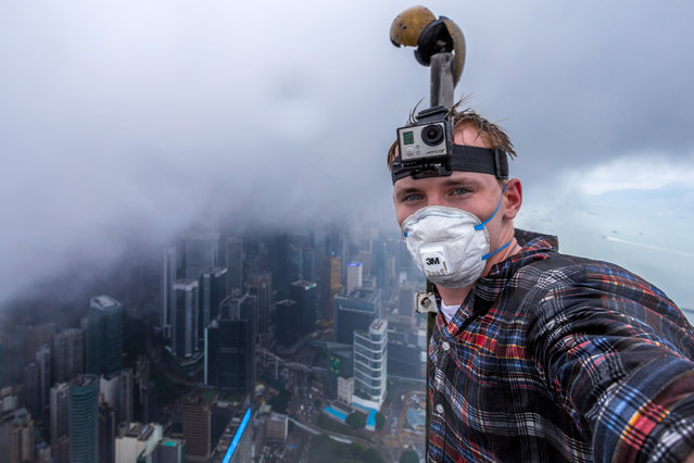 Andrej Ciesielski on top of the Hong Kong skyscraper surrounded by toxic smog. (Photo by Andrej Ciesielski/Caters News Agency)