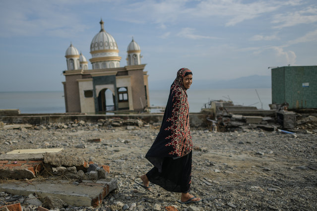 "A resident walks past a damaged mosque by the tsunami-devastated coast in Palu, Indonesia's Central Sulawesi on October 4, 2018, after an earthquake and tsunami hit the area on September 28. The death toll in Indonesia's twin quake-tsunami disaster passed 1,400 Wednesday, with time running out to rescue survivors and the UN warning of ""vast"" unmet needs that have fuelled looting. (Photo by Mohd Rasfan/AFP Photo)"