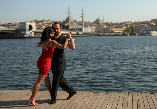A couple dance by the Golden Horn leading to the Bosphorus Strait separating Europe and Asia, in Istanbul, Friday, May 14, 2021. (Photo by Emrah Gurel/AP Photo)