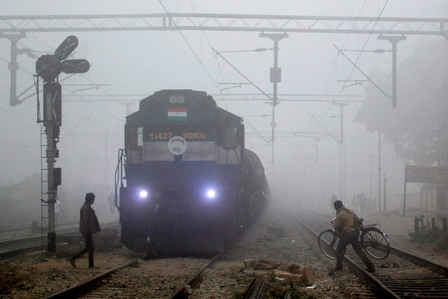 People cross a railway track in front of an arriving train on a foggy winter morning in Allahabad, India November 30, 2016. (Photo by Jitendra Prakash/Reuters)