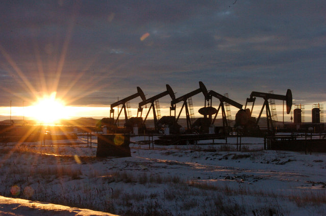 This January 14, 2015 file photo shows oil pump jacks in McKenzie County in western North Dakota. Dozens of European lawmakers, business executives and union leader called Tuesday for the United States to cut its greenhouse gas emissions by 50% in the coming decade compared with 2005 levels. (Photo by Matthew Brown/AP Photo/File)