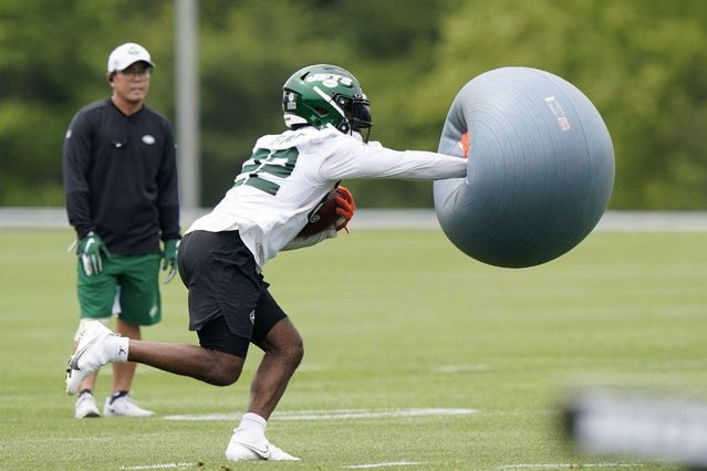New York Jets running back La'Mical Perine fends off an airborne exercise ball thrown at him as he carries the ball during NFL football practice, Wednesday, June 2, 2021, in Florham Park, N.J. (Photo by Kathy Willens/AP Photo)