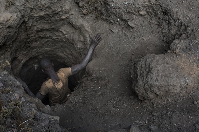 """A """"creuseur"""", or digger, descends into a tunnel at the mine in Kawama, Democratic Republic of Congo on June 8, 2016. The cobalt that is extracted is sold to a Chinese company, CDM, that is a direct supplier to Apple and Samsung. Cobalt is used in the batteries for electric cars and mobile phones. Working conditions are dangerous with no safety equipment or structural support for the tunnels. The diggers are paid on average US$2-3/day. (Photo by Michael Robinson Chavez/The Washington Post)"""