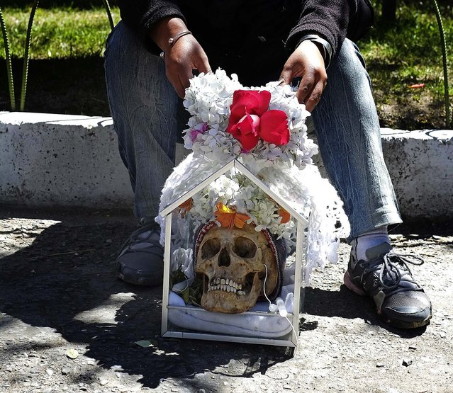 "A woman holds a skull during a ""Dia de los natitas"" (Day of the Skull) ceremony at the Cementerio General of La Paz. (Photo by David Mercado/Reuters)"