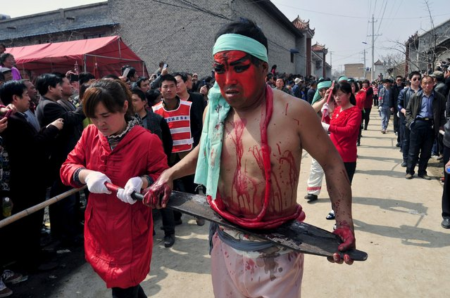 "A folk performer (front R) with make-up and props takes part in a ""Blood Shehuo"" parade, during a performance in Linyi county, Shanxi province March 21, 2015. ""Shehuo"" is the common name of Chinese traditional activities consisting of folk performances in northern China. The ""Blood Shehuo"" performers use make-up and props to re-enact scenes of horror in classic Chinese novels like Water Margin. (Photo by Reuters/Stringer)"