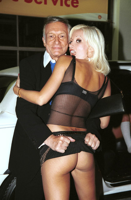 Publisher Hugh Hefner and girlfriend Holly Madison flash outside The Standard Hotel on September 24, 2003.  (Photo by David Klein/Getty Images)