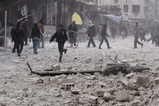 Residents make their way over debris at a site hit by what activists said was an air strike by the forces of Syria's President Bashar al-Assad in the Duma neighbourhood of Damascus January 4, 2015. (Photo by Badra Mamet/Reuters)