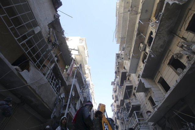 Residents inspect damage after airstrikes by pro-Syrian government forces in the rebel held Al-Shaar neighborhood of Aleppo, Syria February 4, 2016. (Photo by Abdalrhman Ismail/Reuters)
