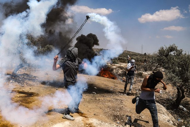 A Palestinian protester returns a tear gas canister toward Israeli forces during confrontaions with them in the town of Beita, near the occupied West Bank city of Nablus, opposite the newly-established Israeli wildcat settler outpost of Eviatar, on July 16 2021. (Photo by Jaafar Ashtiyeh/AFP Photo)