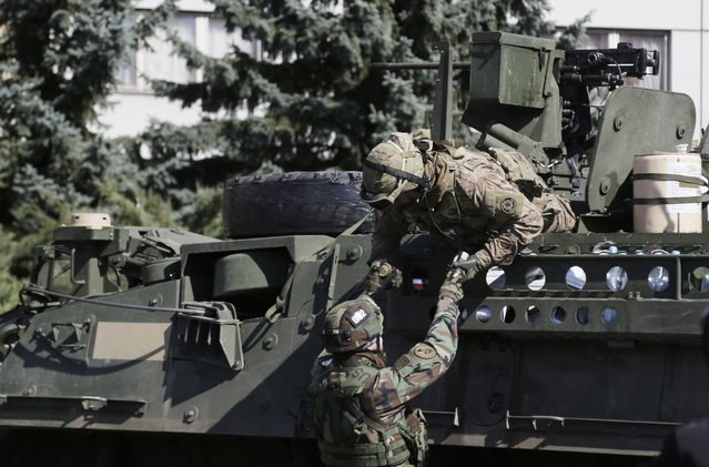 A Czech Republic's soldier hands over beer to a US army soldier upon arrival of their convoy in Prague, Czech Republic, Monday, March 30, 2015. (Photo by Petr David Josek/AP Photo)