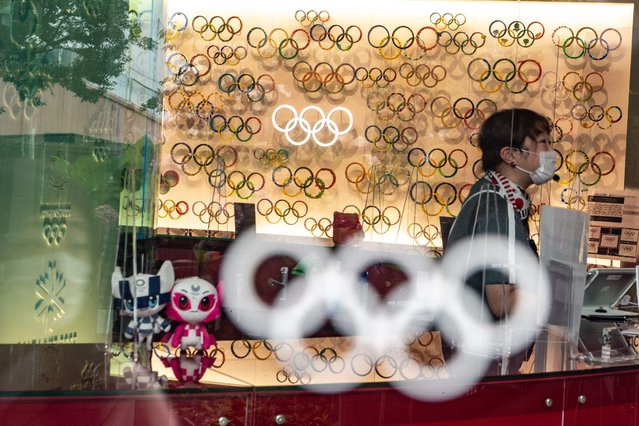 An employee is seen among Olympic Rings and Tokyo 2020 mascots at the Japan Olympic Museum in Tokyo on July 8, 2021. (Photo by Philip Fong/AFP Photo)