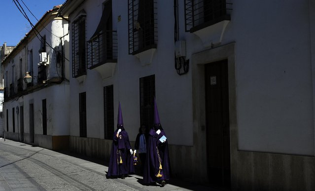 "Hooded penitents from ""El Calvario"" brotherhood walks in their way to the church before a Holy Week procession in Cordoba, Spain, Wednesday, April 1, 2015. (Photo by Manu Fernandez/AP Photo)"