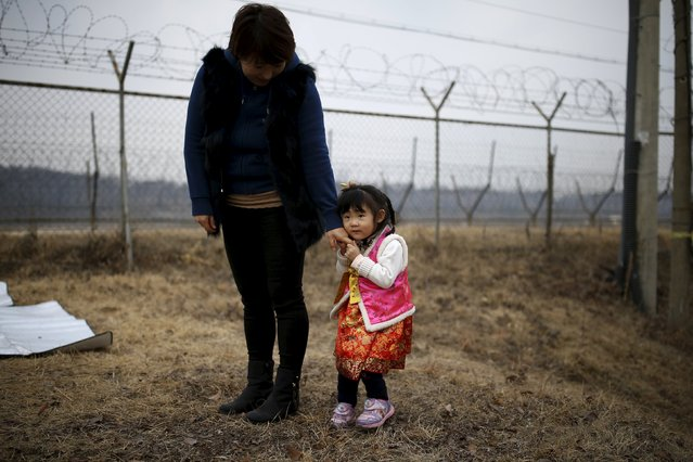 A girl dressed in a Hanbok, a Korean traditional costume, holds her mother's hand in front of a barbed-wire fence, after a memorial service for North Korean family members, near the demilitarized zone separating the two Koreas, in Paju, February 8, 2016, on the occasion of Seolnal, the Korean Lunar New Year's day. Millions of South Koreans travelled to their hometowns during the three-day holiday. Seolnal is one of the traditional holidays when most Koreans visit their hometowns to be united with their families and hold memorial services for their deceased ancestors. (Photo by Kim Hong-Ji/Reuters)