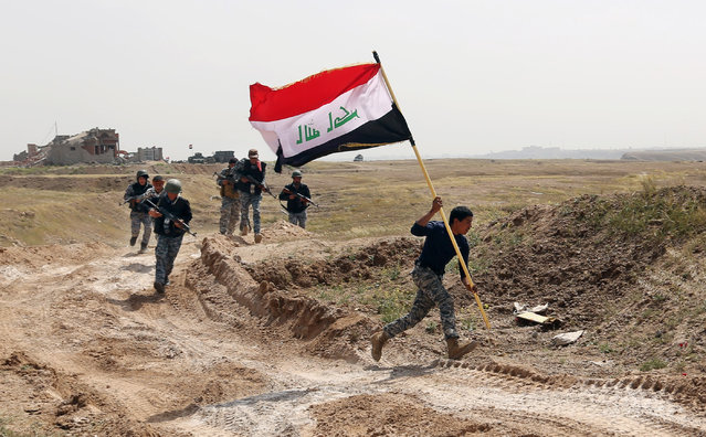 A member of the Iraqi security forces runs to plant the national flag as they surround Tikrit during clashes to regain the city from Islamic State militants, 80 miles (130 kilometers) north of Baghdad, Iraq, Monday, March 30, 2015. (Photo by Khalid Mohammed/AP Photo)