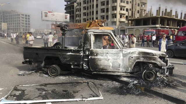 People look at a burnt-out police patrol vehicle after clashes in Yemen's southern port city of Aden February 9, 2016. The recapture of Aden by Gulf Arab coalition troops last summer has failed to provide any respite from Yemen's civil war, with residents facing a wave of bomb and gun attacks that is crippling efforts to stabilize the city. (Photo by Reuters/Stringer)