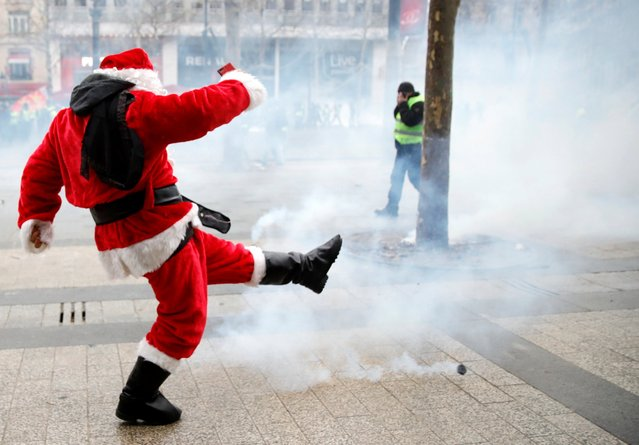 """A protester dressed as Santa Claus takes part in a demonstration by the """"yellow vests"""" movement in Paris, France, December 15, 2018. (Photo by Gonzalo Fuentes/Reuters)"""