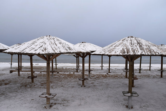 Beach umbrellas are covered with snow at the beach in the town of Artemida, Greece January 8, 2017. (Photo by Vassilis Triandafyllou/Reuters)