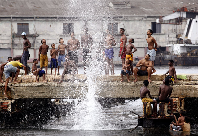 Youths compete for the highest splash as they jump into the water at Havana's port, July 2009. (Photo by Desmond Boylan/Reuters)