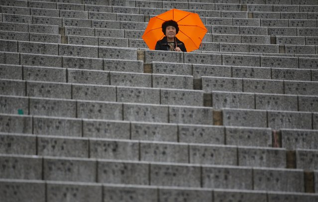 A South Korean Christian holding an umbrella waits for starting an annual Easter mass service in Seoul April 5, 2015. (Photo by Kim Hong-Ji/Reuters)