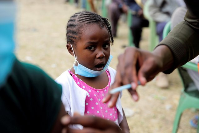 A girl reacts as her father receives an AstraZeneca/Oxford coronavirus disease (COVID-19) vaccine, donated to Kenya by the UK government, in Nairobi, Kenya, August 8, 2021. (Photo by Baz Ratner/Reuters)