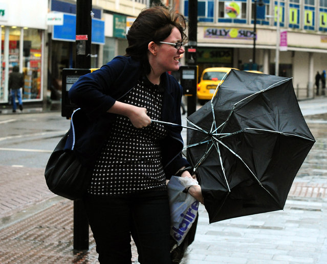A woman struggles with an umbrella in the wind and rain while walking in Derby city centre, onDecember 23, 2013. (Photo by Rui Vieira/PA Wire)