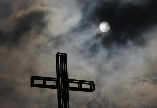 Dark clouds partially cover the sun above a church on Easter Sunday April 5, 2015 in suburban Quezon city, north of Manila, Philippines. (Photo by Aaron Favila/AP Photo)