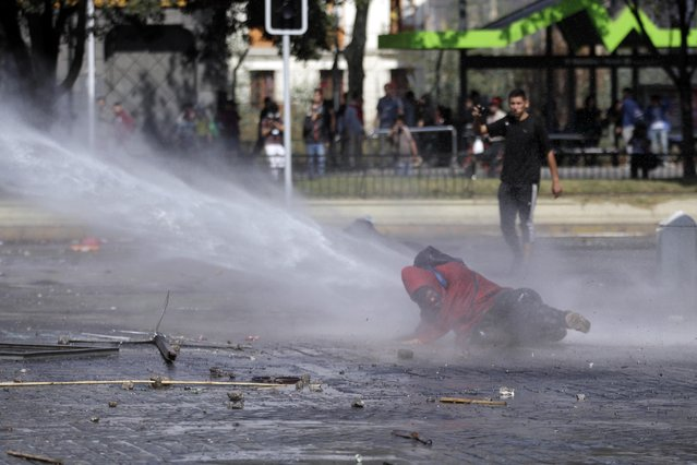 A protester is taken down by a water cannon during a march, in Santiago, Chile, Thursday, April 16, 2015. (Photo by Luis Hidalgo/AP Photo)