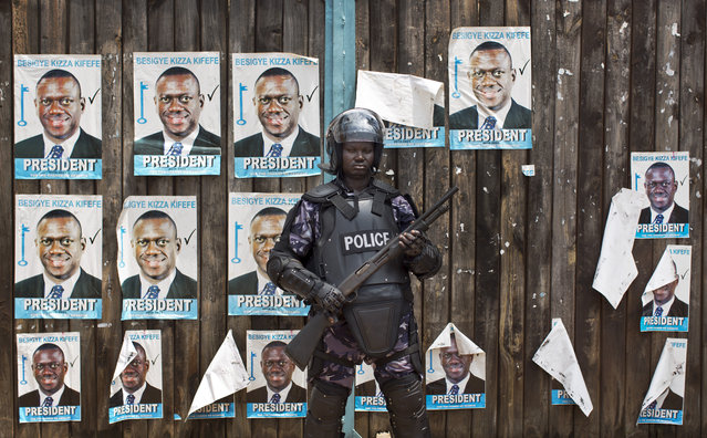 A Ugandan riot policeman blocks the gate of the party headquarters of opposition leader Kizza Besigye, shortly after raiding the premises for the second time in a week, in the capital Kampala, Uganda, Monday, February 22, 2016. Party officials told a group of visiting European Union observers that the security officials had raided the office and arrested eight party staff, just hours before the EU observers had been scheduled to meet with party officials at the building. (Photo by Ben Curtis/AP Photo)