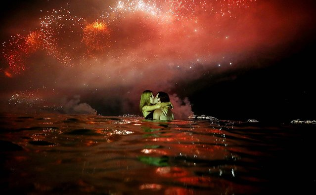 A couple kisses while watching fireworks explode minutes after midnight along Copacabana Beach during New Year's celebrations in Rio de Janeiro. (Photo by Mario Tama/Getty Images)