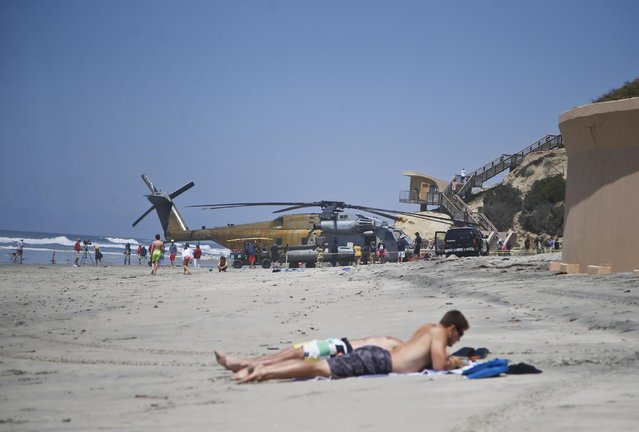 A Marine Corps helicopter sits in the sand where it made an emergency landing Wednesday, April 15, 2015 in Solana Beach, Calif. The CH-53E Super Stallion landed on the shore of this northern San Diego County town shortly after 11:30 a.m. after a low oil-pressure indicator light went on in the cockpit, Marine Corps Air Station Miramar said in a statement. (Photo by Lenny Ignelzi/AP Photo)